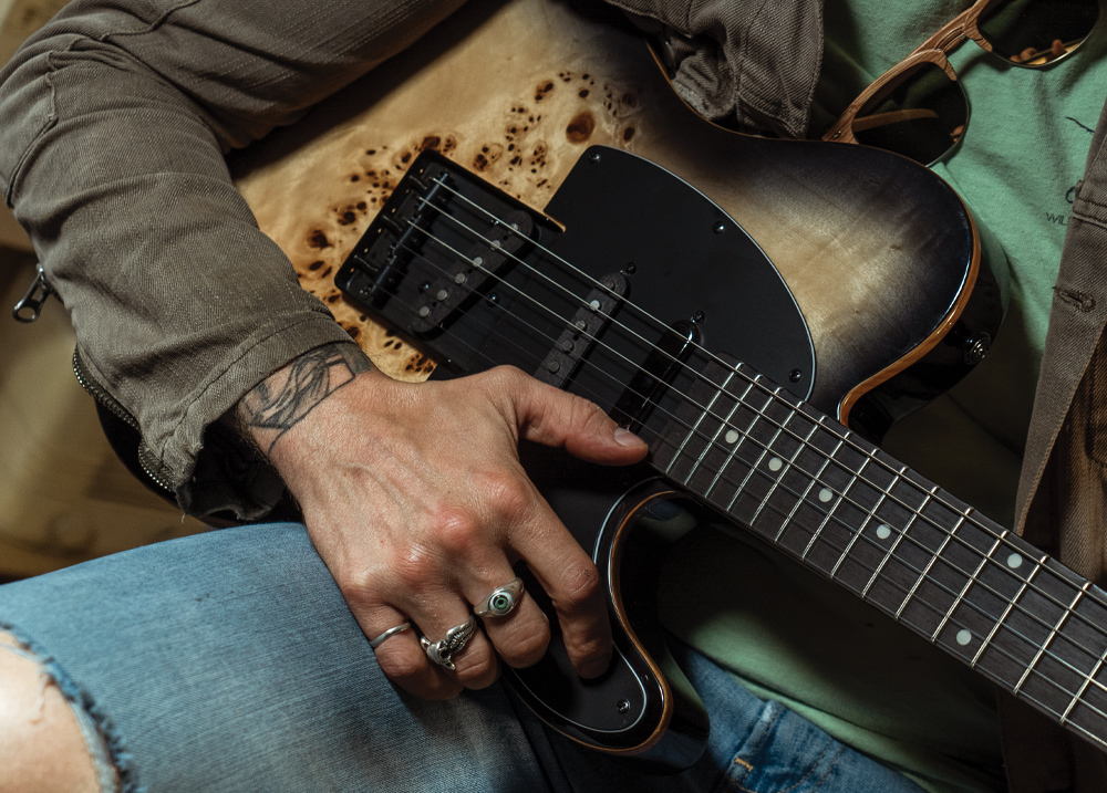 partial view of man holding electric guitar